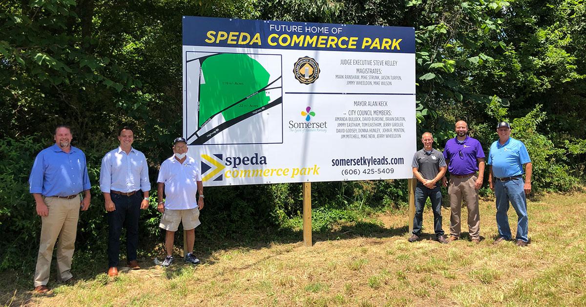 six men standing in front of sign