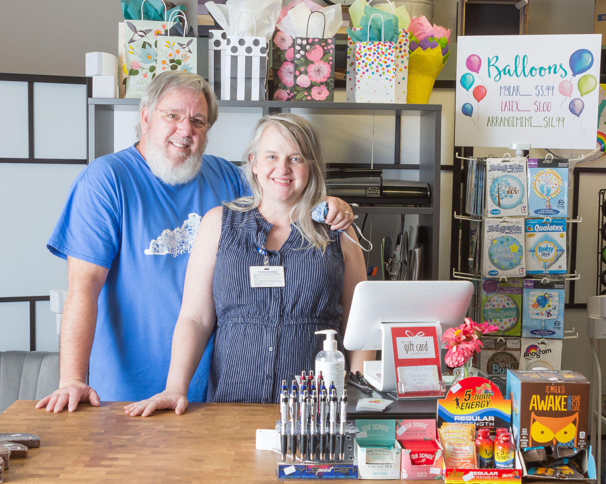 man and woman behind store counter