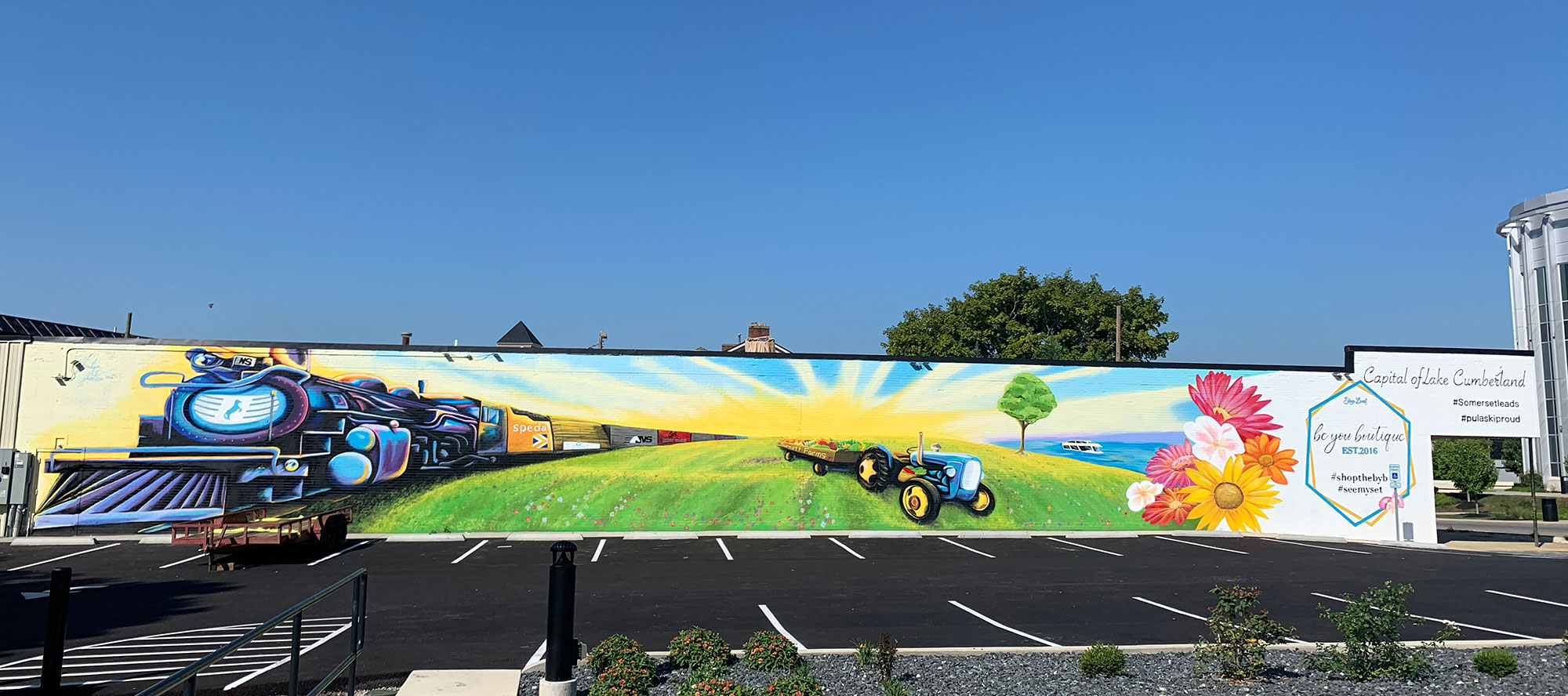 mural painted on side of building with train lake and tractor