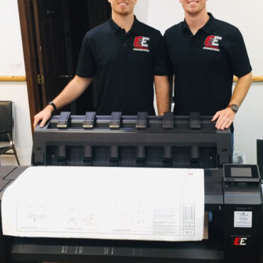 two men standing behind printer
