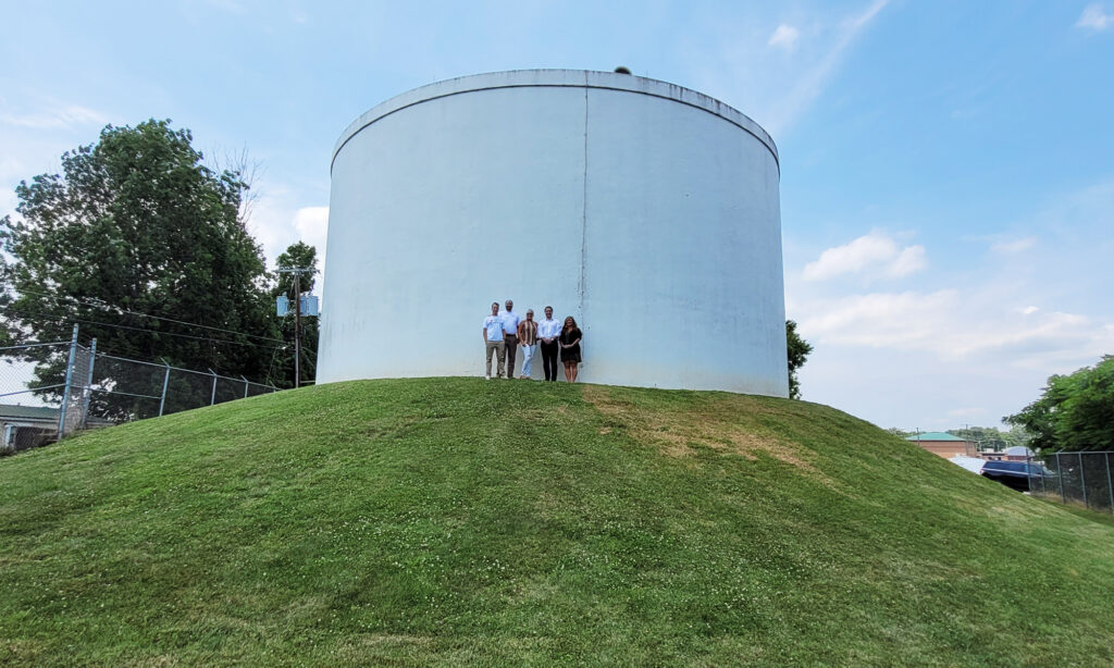 five people standing in front of a water tank