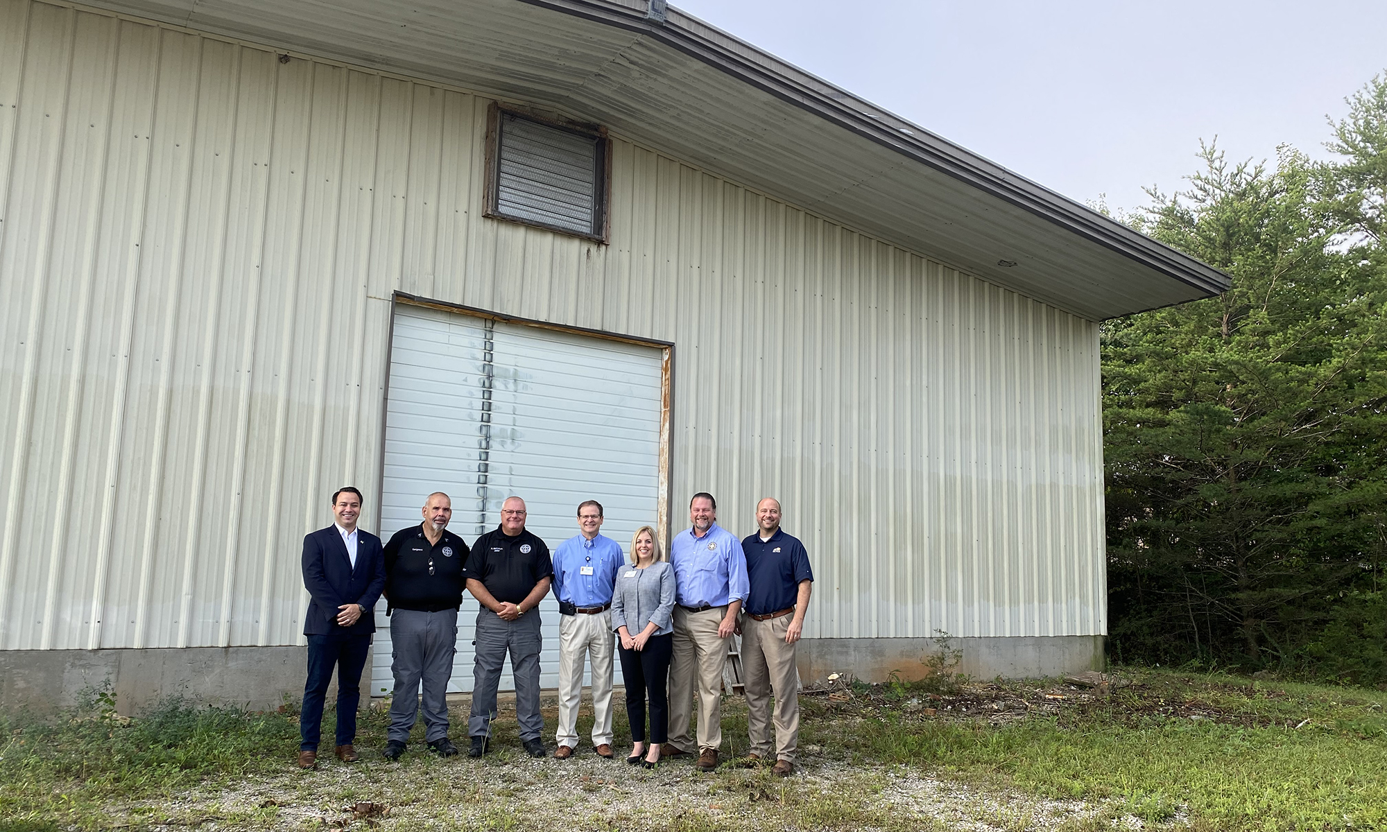 six people standing in front of warehouse
